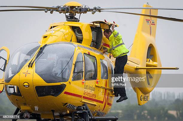 Prince William The Duke of Cambridge performs checks on his helicopter as he begins his new job with the East Anglian Air Ambulance at Cambridge...