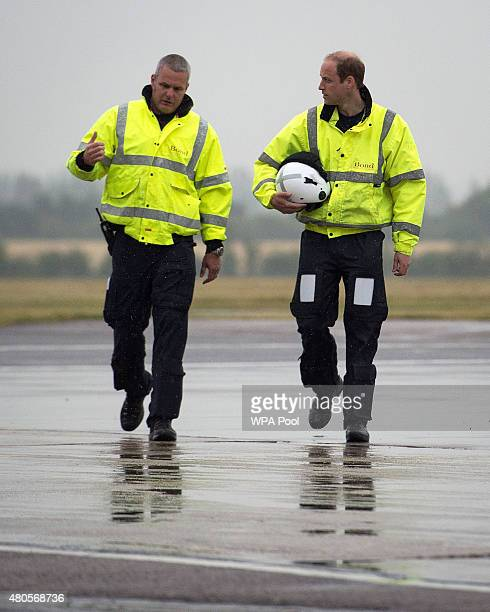 Prince William The Duke of Cambridge walks towards his helicopter with Captain Dave Kelly as he begins his new job with the East Anglian Air...