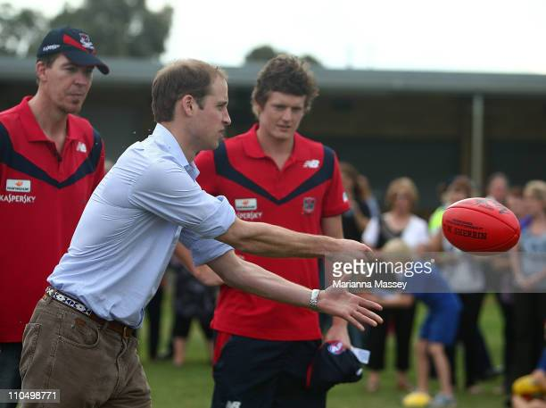 Prince William visits with locals and has a go at some Aussie Rules Football at the Marrabit Recreational grounds where the town people gathered for...