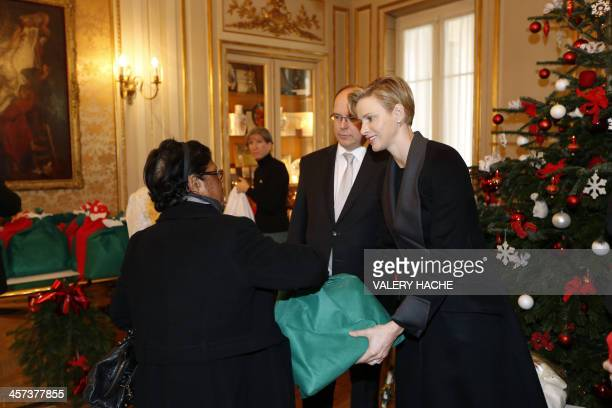 Prince's Albert II and Princess Charlene of Monaco give a Christmas present to a Monaco resident on December 17 in Monaco AFP PHOTO / VALERY HACHE