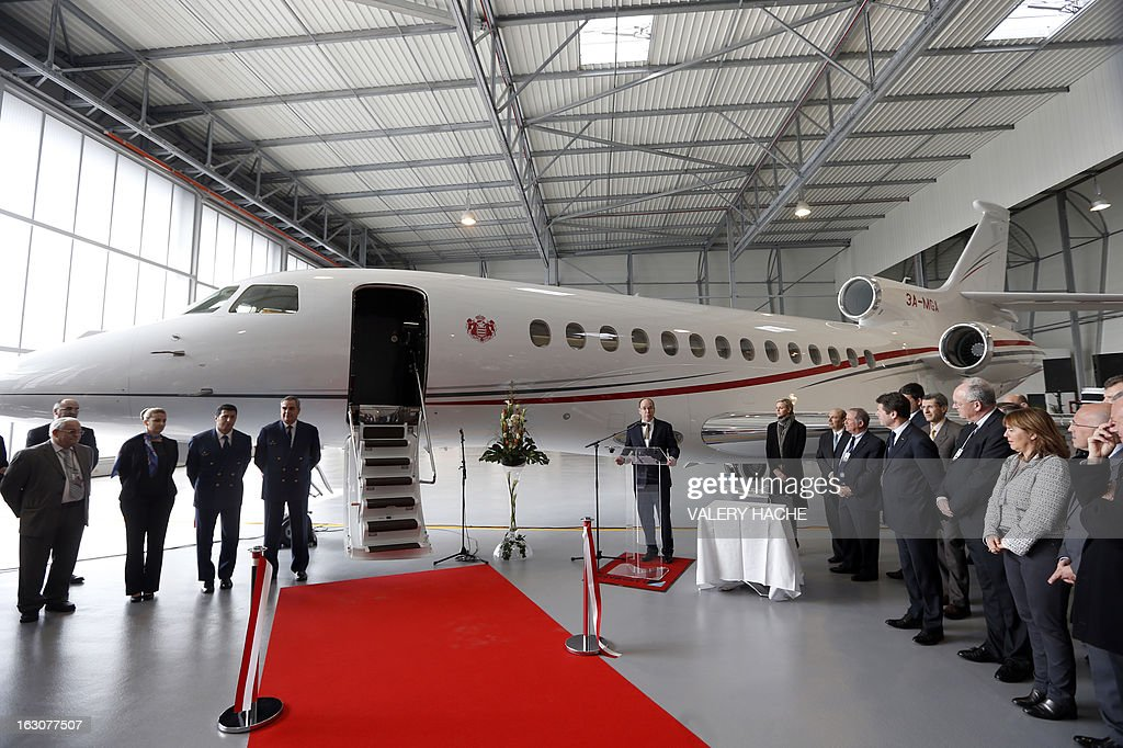Prince's Albert II of Monaco (C) delivers a speech on March 4, 2013 next to his wife Princess Charlene during the presentation of the Monegasque Princely family's new 'Falcon 7X' plane and its hangar in Nice airport, southeastern France.