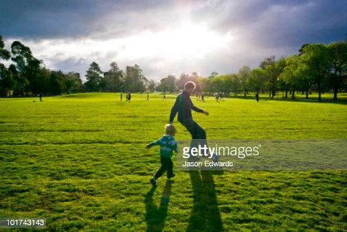 A father and son play football in a city park on a stormy winters day. : Stock Photo