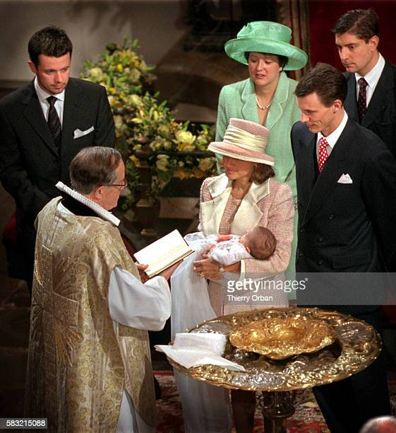 Princess Alexandra holds her son over the font