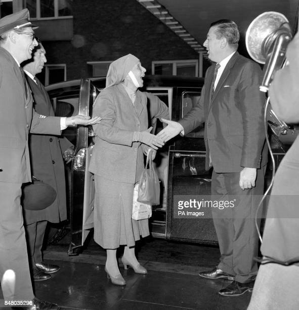 Princess Alice of Greece mother of the Duke of Edinburgh extends a hand in greeting as she steps from her car at Heathrow Airport before flying off...