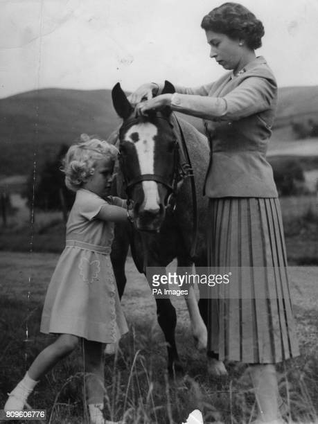 Princess Anne helps her mother Queen Elizabeth II fit the bridle to the pony 'Greensleeves' the the grounds of Balmoral Castle during the Royal...