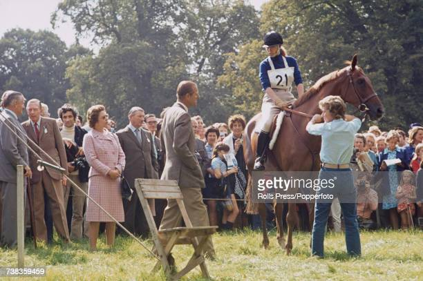 Princess Anne pictured sitting on her horse Doublet as she talks to her father Prince Philip with Queen Elizabeth II looking on during her...