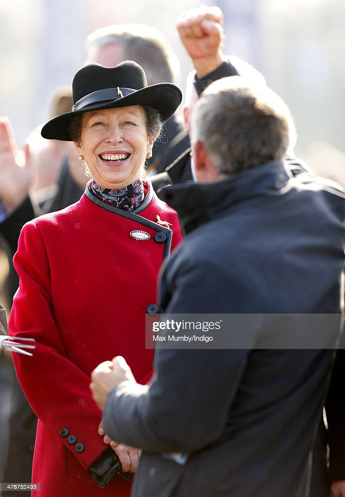 Princess Anne, The Princess Royal watches the racing alongside a cheering racegoer as she attends Day 4 of the Cheltenham Festival at Cheltenham Racecourse on March 14, 2014 in Cheltenham, England.