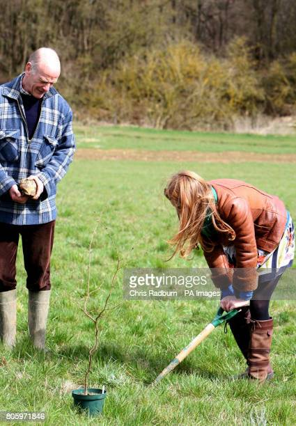 Princess Beatrice of York plants a hazel tree sapling alongside John Tucker Operations Director of The Woodland Trust during a visit to The Woodland...