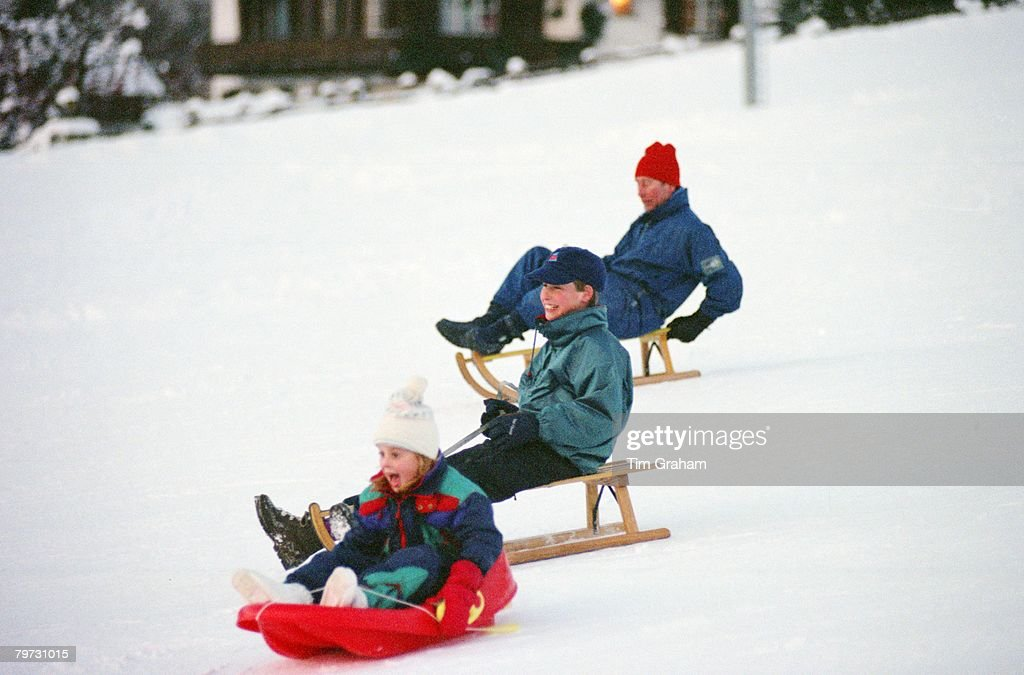 Princess Beatrice Prince William and Prince Charles Prince of Wales sledging on holiday in Klosters