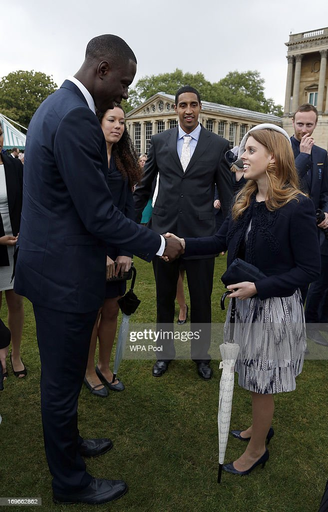 Princess Beatrice speaks to members of the Team GB Olympic Basketball Team, including Kieron Achara (C) during a garden party held at Buckingham Palace, on May 30, 2013 in London, England.