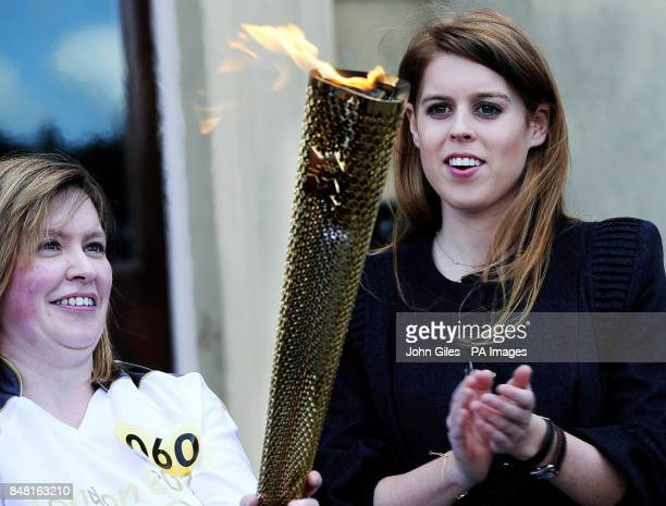 Princess Beatrice welcomes torch bearer Janet Baker and the Olympic Flame on the steps of Harewood House near Leeds during the Olympic Torch Relay