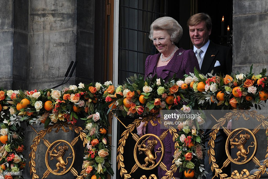 Princess Beatrix of the Netherlands stands in front of her son King Willem-Alexander of the Netherlands as she greets the crowd on April 30, 2013 gathered on Dam Square from the balcony of the Royal in Palace Amsterdam, following her official abdication.