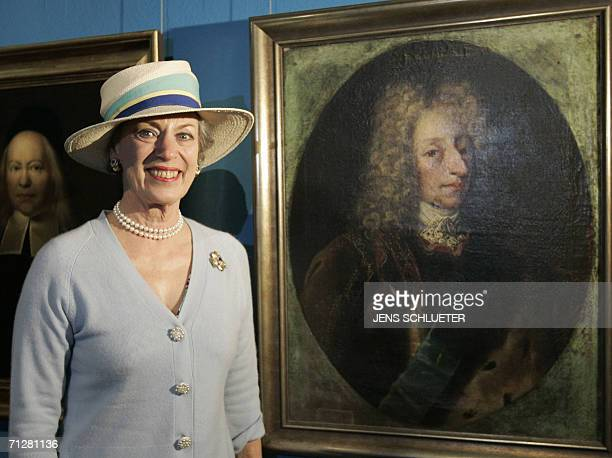 Princess Benedikte of Denmark poses beside a painting displaying Danish king Frederik IV in Halle eastern Germany 23 June 2006 The Princess attends...