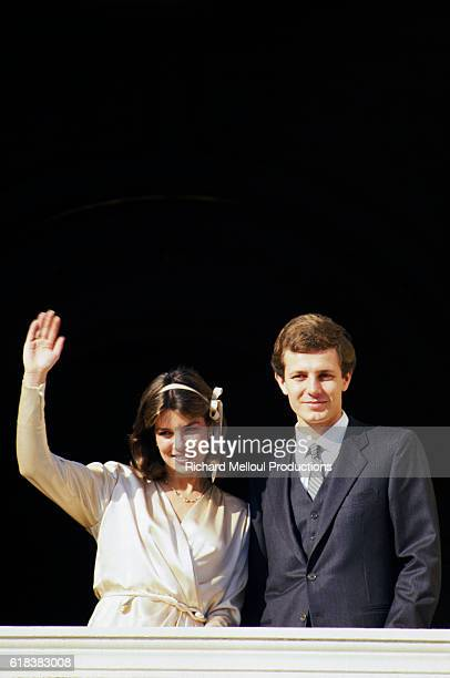 Princess Caroline of Monaco waves to admirers as she stands on a balcony with her new husband Stefano Casiraghi at the Royal couple's wedding