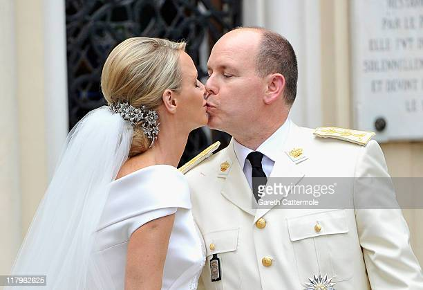 Princess Charlene of Monaco and Prince Albert II of Monaco kiss as they leave Sainte Devote church after their religious wedding ceremony at the...