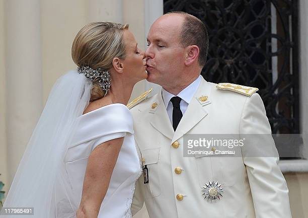 Princess Charlene of Monaco and Prince Albert II of Monaco kiss as they leave Sainte Devote church after the religious ceremony of their Royal...