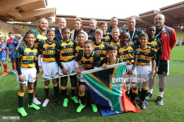 Princess Charlene of Monaco and Prince Albert II of Monaco pose with young rugby players for the International Rugby tournament Tournoi Sainte Devote...