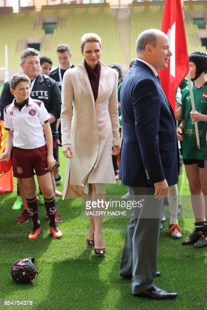 Princess Charlene of Monaco and Prince Albert II of Monaco salute young rugby players during the International Rugby tounament of Monaco on March 18...