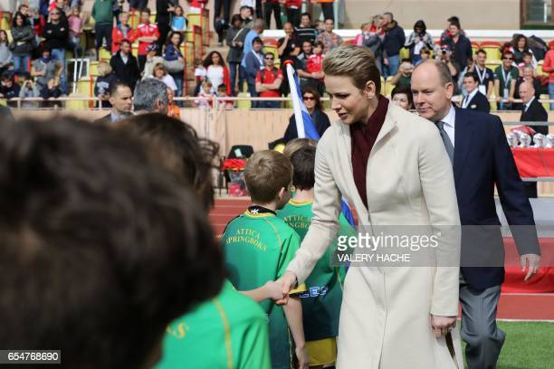Princess Charlene of Monaco and Prince Albert II of Monaco shake hands as they arrive for the International Rugby tournament Tournoi Sainte Devote at...