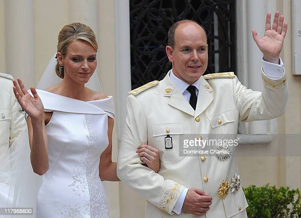 Princess Charlene of Monaco and Prince Albert II of Monaco wave to the crowds as they leave Sainte Devote church after the religious ceremony of...