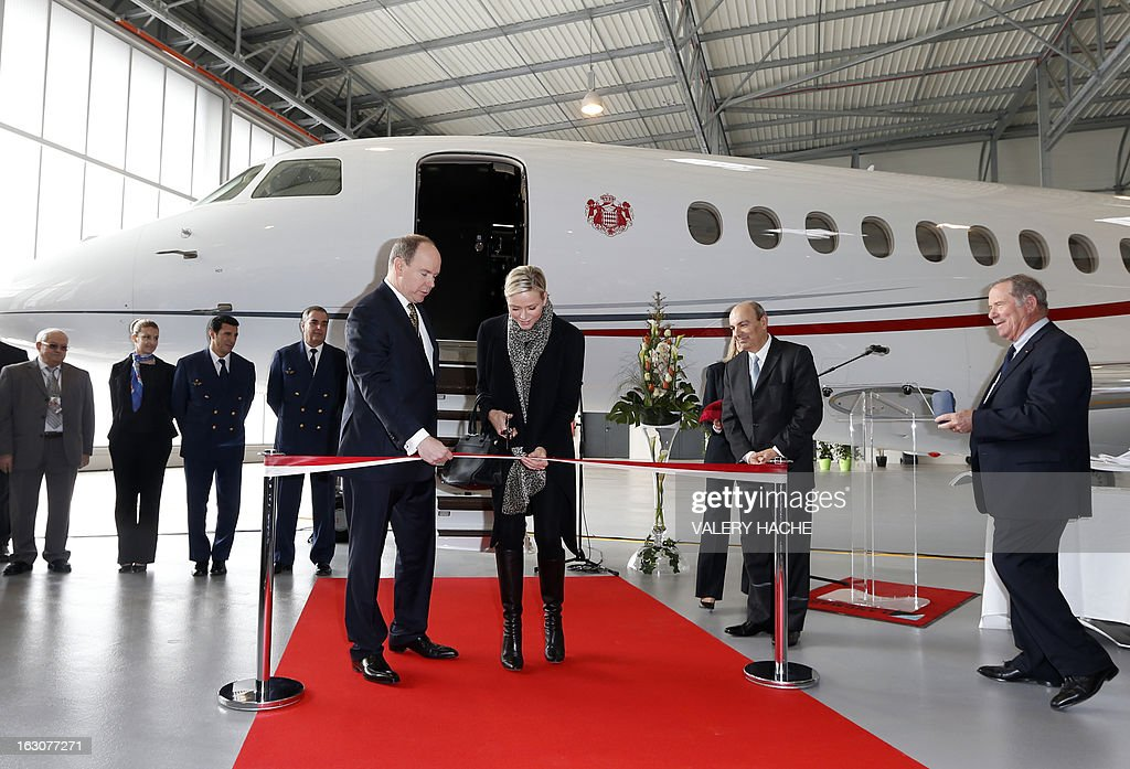 Princess Charlene of Monaco (C) cuts the ribbon on March 4, 2013 as she attends with her husband Prince's Albert II of Monaco, the presentation of the Monegasque Princely family's new 'Falcon 7X' plane and its hangar in Nice airport, southeastern France.