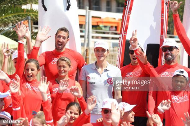 Princess Charlene of Monaco flanked by Olympic swimmer Alain Bernard and French swimmer Virginie Dedieu attends the 'Water Safety' day for the...
