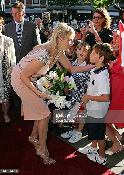 Princess Charlene of Monaco kisses a young boy as she arrives at the opening of the Grace Kelly exhibition at Bendigo Museum on March 10 2012 in...