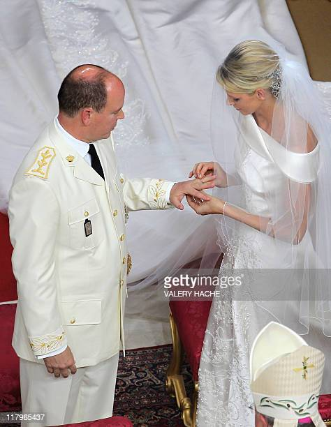 Princess Charlene of Monaco puts the ring on the finger of Prince Albert II of Monaco during their religious wedding at the Main Courtyard of the...