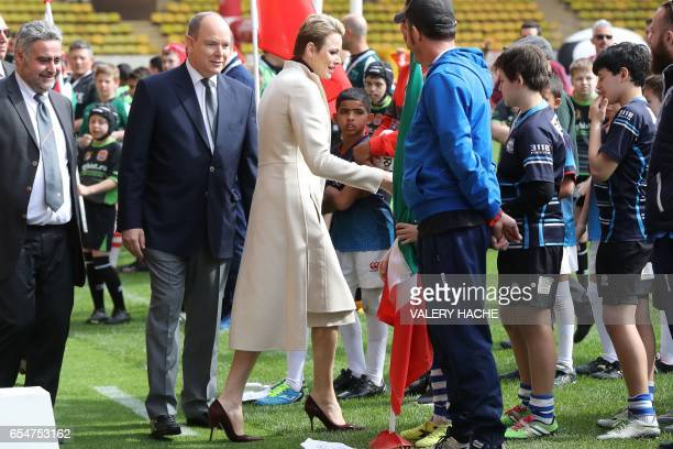 Princess Charlene of Monaco shakes hand of young rugby players next to Prince Albert II of Monaco during the International Rugby tounament of Monaco...