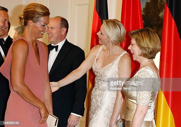 Princess Charlene of Monaco welcomes Franziska van Almsick while German First Lady Daniela Schadt smiles prior to the gala dinner at Schloss Bellevue...
