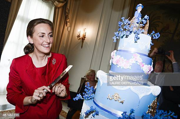 Princess Claire of Belgium cuts on April 30 2014 the birthday cake with a statuette portraying Queen Elizabeth II on top at a birthday party in honor...