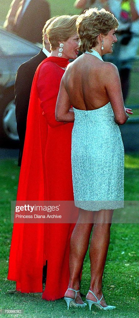 Princess Diana (1961 - 1997, right) arrives at the Serpentine Gallery, London, June 1995. She is wearing a grey, beaded, halter-neck dress by Catherine Walker.