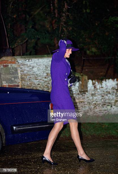 Princess Diana clutches her hat to stop it from blowing away whilst walking to a Christmas service at Sandringham