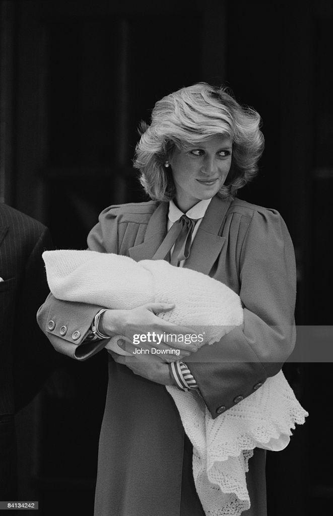 Princess Diana (1961 - 1997) leaves St Mary's Hospital, London with her newborn son Prince Harry, 17th September 1984. She is wearing a red coat by Jan van Velden.