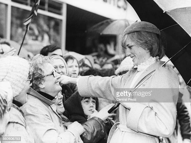 Princess Diana of Wales smiling as she prepares to embrace a woman in the crowd on the streets of Carmarthen Wales October 29th 1981