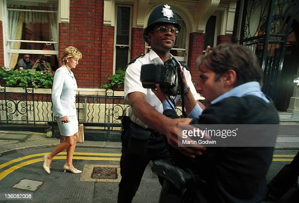 Princess Diana on the day her divorce from the Prince of Wales was announced with a policeman holding back a photographer St James' London 12th July...