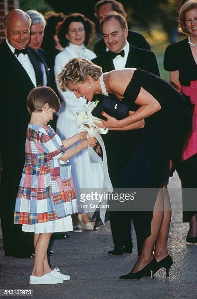 Princess Diana receives a bouquet from a young girl as she arrives for a gala event at the Serpentine Gallery London 29th June 1994 The princess is...