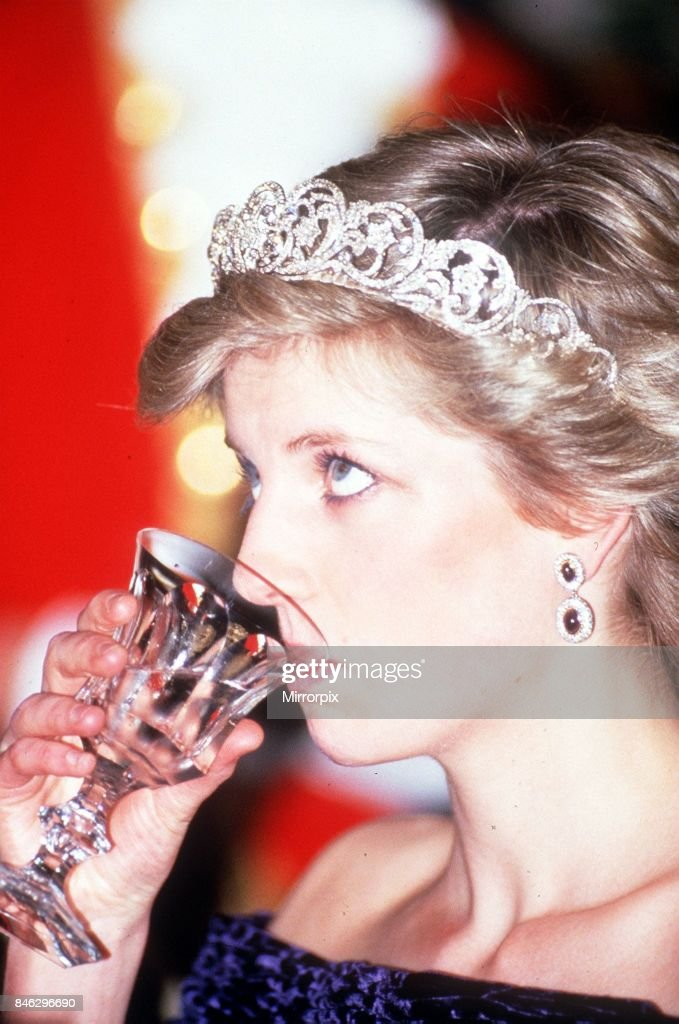Princess Diana visits Portugal at a banquet hosted by the President at Ajuda Palace Lisbon,drinking wine wearing a tiara looking up portrait,11th February 1987.