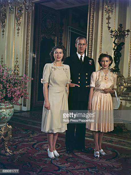 Princess Elizabeth and her betrothed Lieutenant Philip Mountbatten pose together with Princess Margaret at Buckingham Palace in London after...
