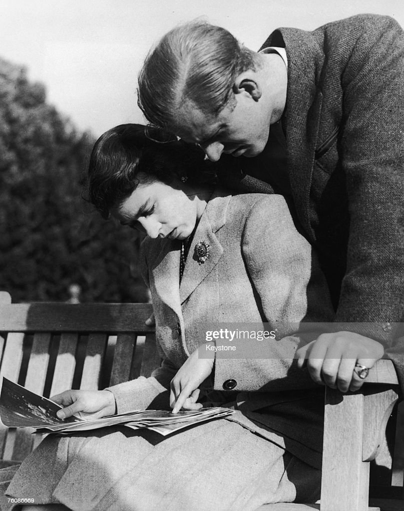 Princess Elizabeth (later Queen Elizabeth II) and her husband, Philip Mountbatten, study their wedding photographs while on honeymoon in Romsey, Hampshire, November 1947.