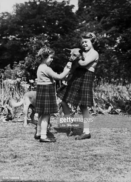 Princess Elizabeth and her sister Princess Margaret wearing kilts and holding a dog at the Royal Lodge Windsor UK June 1936
