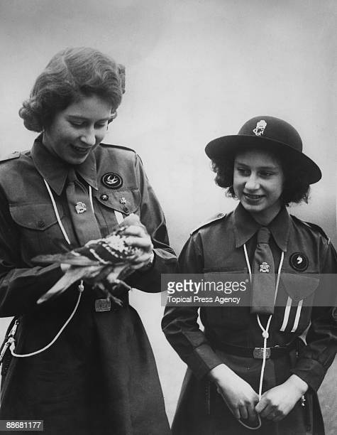 Princess Elizabeth and her younger sister Princess Margaret Rose prepare to release a carrier pigeon with a message to Chief Guide Lady Olave...
