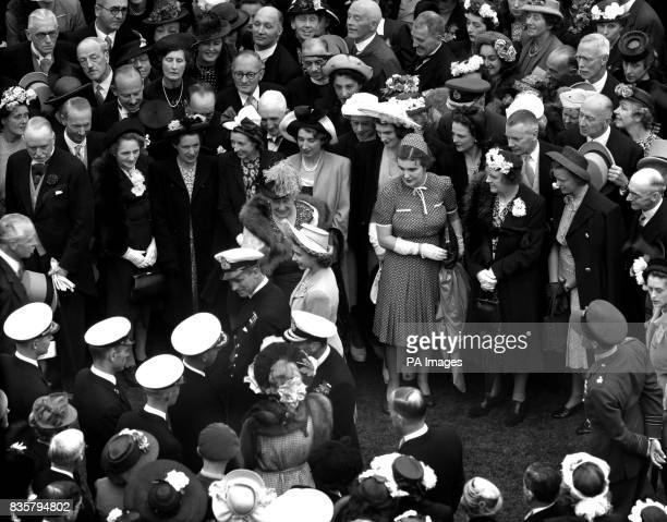 Princess Elizabeth and Lieutenant Philip Mountbatten are accompanied by King George VI as they walk through the assembly of guests on the lawn of...