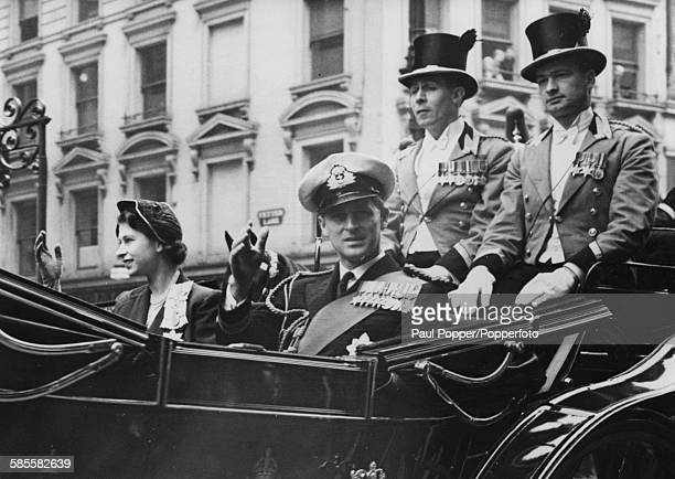 Princess Elizabeth and Prince Philip the Duke of Edinburgh wave from their open carriage during a state drive to St Paul's Cathedral for the...