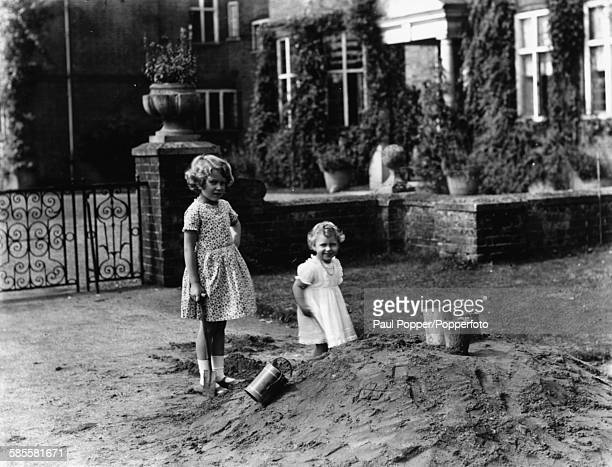 Princess Elizabeth and Princess Margaret playing together outdoors beside a pile of sand August 12th 1932