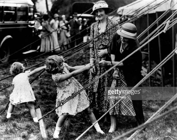 Princess Elizabeth and Princess Margaret playing with tent ropes at a fair in Scotland Princess Margaret was born at Glamis Castle Angus the...