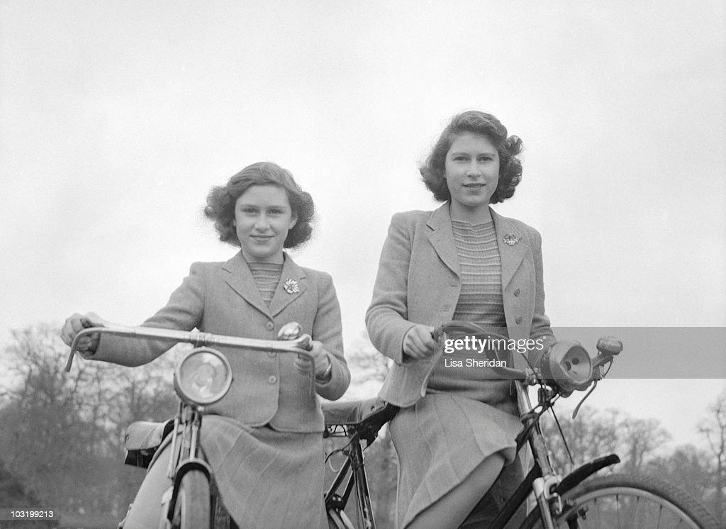 Princess Elizabeth and Princess Margaret pose on bicycles in Windsor England on April 4 1942