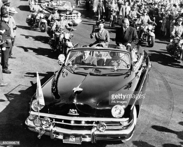Princess Elizabeth and the Duke of Edinburgh sit up on the back of the rear seat of their open Cadillac during their drive through Riverdale Park in...