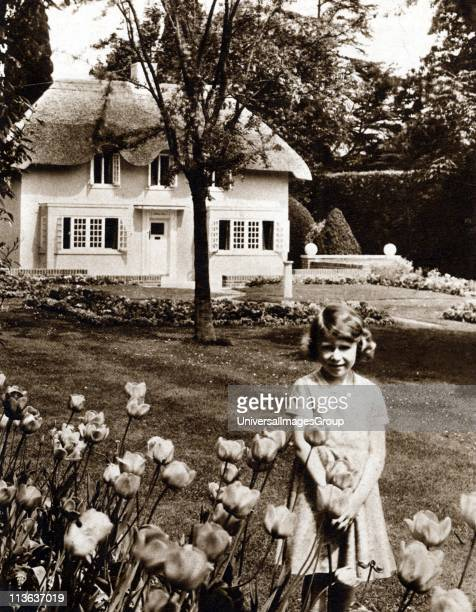 Princess Elizabeth as a child in the garden of Royal Lodge Windsor with Y Bwthyn Bach the play house given by the people of Wales