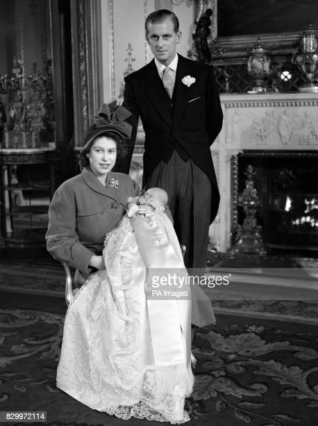 Princess Elizabeth holding Prince Charles in his Christening gown with her husband the Duke of Edinburgh behind